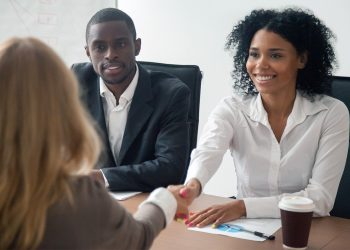 two women shaking hands in a business meeting