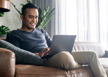 man at home using his laptop